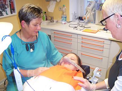 Zeigt eine Patientin auf dem Behandlungsstuhl mit der Nasenmaske